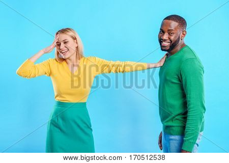 Cheerful young couple is standing and flirting. Shy girl is touching her head and smiling. Guy is looking at camera with joy. Isolated on blue background