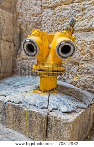 Funny yellow hydrant on a street of the old city of Jerusalem, Israel.