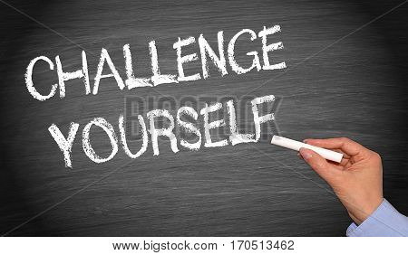 Challenge yourself - chalkboard with female hand writing text