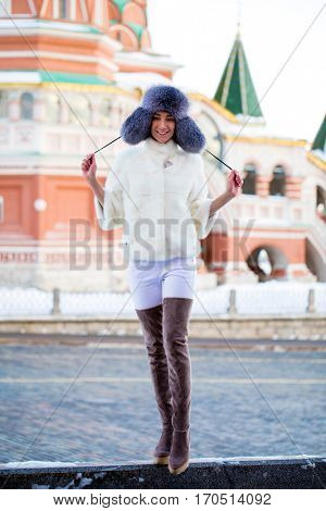 Closeup portrait of young brunette woman in white fur coat, winter park outdoors