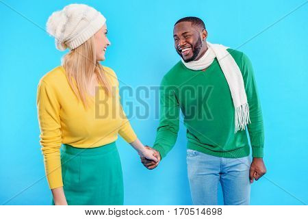 Stay with me. Affectionate young african man is holding female hand. He is looking at woman with love and smiling. Isolated