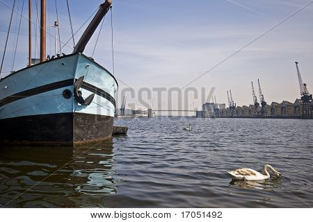 boat in the harbour with swans and crane views
