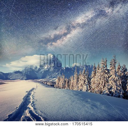 starry sky in winter snowy night. fantastic milky way in the New Year's Eve. Starry sky snowy winter night. The Milky Way is a fantastic New Year's Eve. Winter road in the mountains