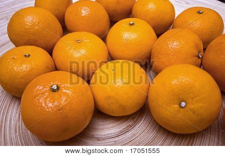 wooden flat dish with large juicy clementines