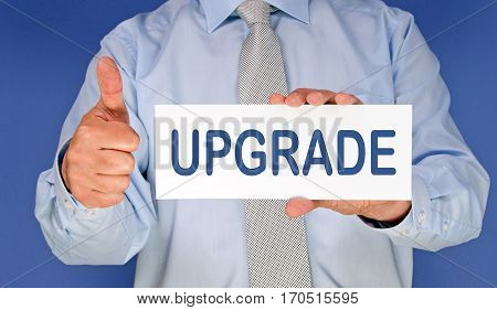 Upgrade - Businessman with sign and thumb up