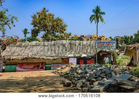 Hampi, India - November 20, 2012: Mud houses with a thatched roof palm trees and piles of debris in Hampi, India. Old outdoor cafe for tourists the perfect place to taste Indian cuisine.