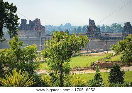 Hampi, India - November 20, 2012: View of Prasanna Narasimha Temple with walking Indian tourists. Ancient ruins of Vijayanagara Empire in Hampi, Karnataka, India.