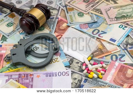 drug and substances prohibited with handcuffs on dollar and euro bills.