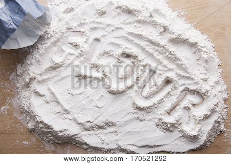 Flour spread on the wooden table with the word flour