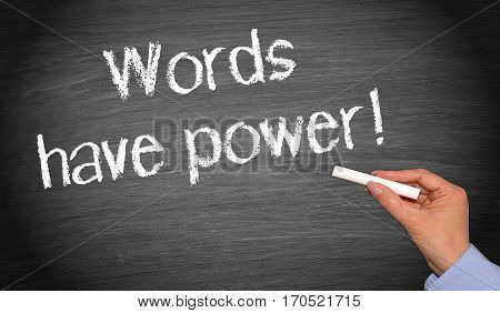 Words have power - female hand writing text on chalkboard
