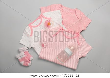 Baby clothes and necessities on light background