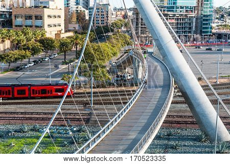 SAN DIEGO, CALIFORNIA - JANUARY 8, 2017:  The San Diego Trolley approaches the Harbor Drive pedestrian bridge, near the San Diego Convention Center and Petco Park.
