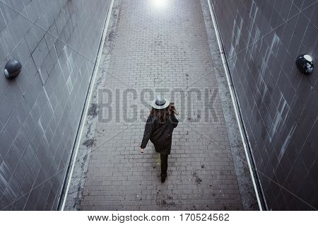 Girl in a hat and autumn coat swiftly and confidently goes up the road, on the background texture of the pavement. Woman crossing passage
