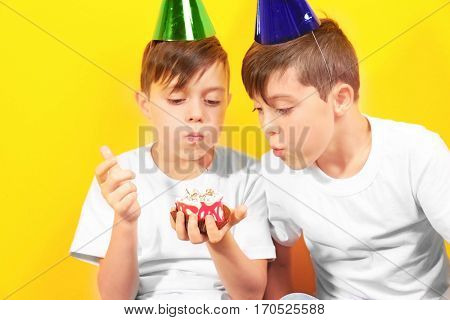 Cute boys with birthday mini cake on yellow background