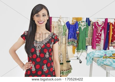 Portrait of pretty Indian female dressmaker standing with hand on hip