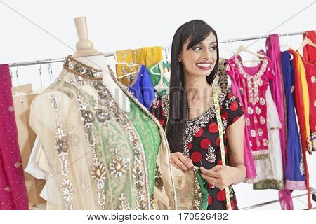 Pretty Indian female dressmaker looking away while working on traditional outfit