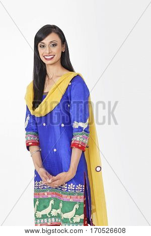 Portrait of beautiful Indian female traditional wear standing against gray background