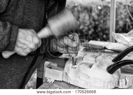 Old carpenter carves a wooden carnival mask.