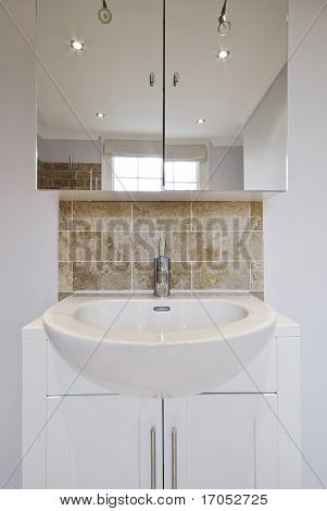 modern ceramic hand wash basin with stone tiles and mirror cupboard