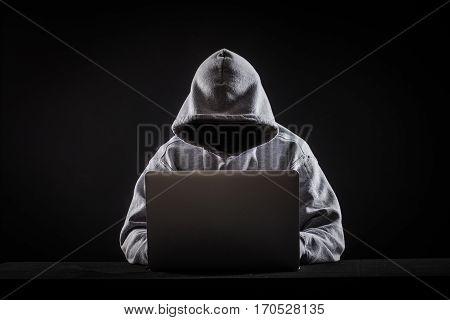 hacker on hack a laptop on black background
