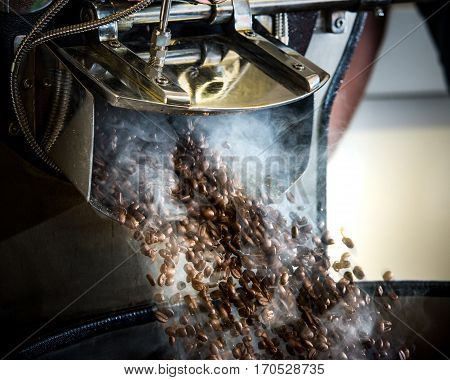 Fresh roasted coffee beans spilling out of roasting machine with smoke