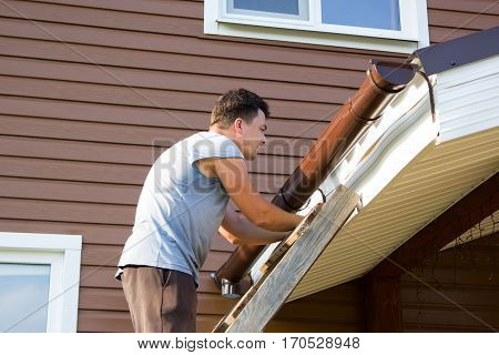 Man Attaches Gutter On Roof Of The Porch