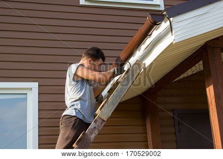 Man Attaches Gutter On Roof Of Porch