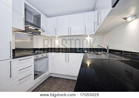 contemporary luxury kitchen in white with black stone worktop