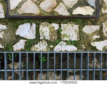 Grate and drain on a stone surface on the ground with weeds growing inbetween the stones with space for text.