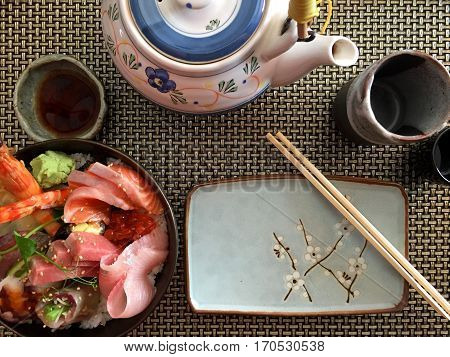 Japanese place setting with a bowl of rice with fish a bowl with soy sauce a dish with chopsticks resting on it a teapot a cup and a small cup for sake. with space for text.