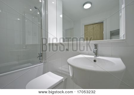 contemporary bathroom with floor to ceiling tiles and white suite
