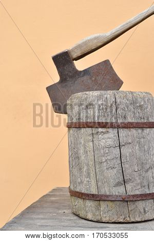 The big axe is inserted into a wooden stump.