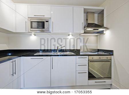 modern luxury kitchen in white with black granite worktop