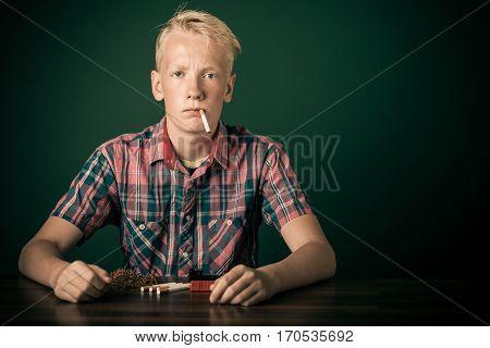 Young Teenage Boy Sitting Smoking