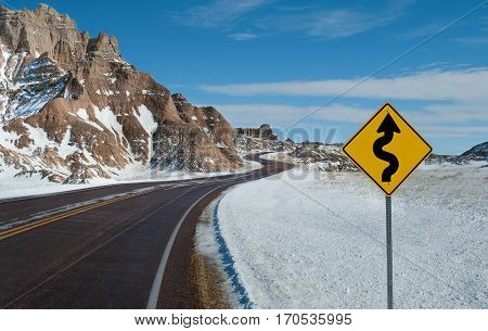 Sharp Curves Warning Sign:  A sign warns of a twisting road ahead on a winter day in Badlands National Park.