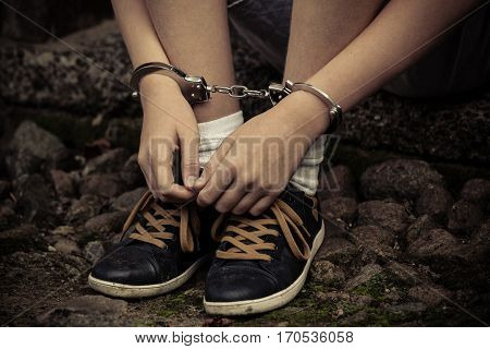 Young Boy In Handcuffs And Sneakers
