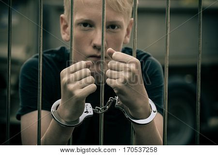 Handcuffed Teenage Boy Behind Bars