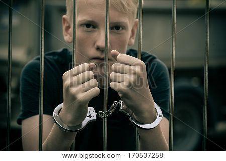Handcuffed Teenage Boy Behind Bars