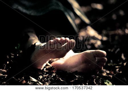 Feet Of A Dead Child In Forest Detritus