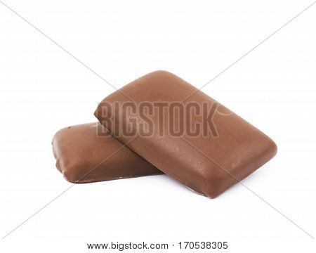 Pile of multiple flat chocolate coated caramel candies isolated over the white background