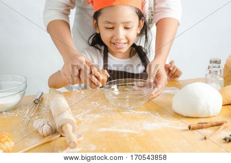 Close up shot of Asian little girl breaking the egg shell for make the bakery shallow depth of field select focus on hand