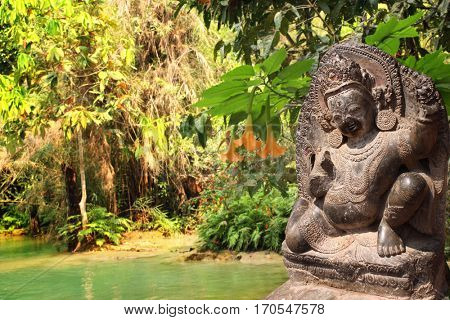 Stone sculpture of dancing hindu god and trees in rainforest