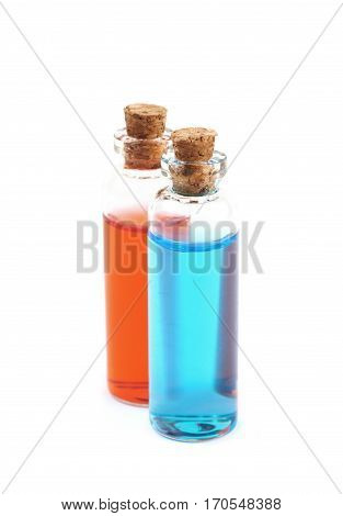 Two tiny vial bottles filled with the colored liquid, composition isolated over the white background