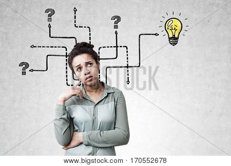 Portrait of a pensive African American girl standing near a concrete wall with arrows leading to question marks nowhere and to a shining light bulb.