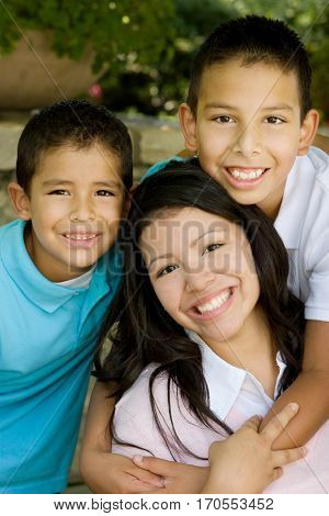 Portrait of a happy Hispanic mother hugging her sons.