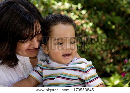 Portrait of a happy Hispanic mother hugging her son.