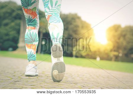 Closeup of female fitness model legs in movement - Runner woman training outside in a park with sunrise preparing to sprint - Focus on the girl's shoe