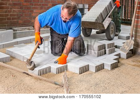 Builder laying new paving stones kneeling down tamping them into position with a heavy mallet on raked sand with the rake in the foreground