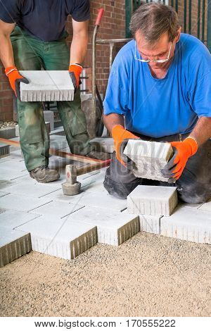 Builder Placing New Paving Stones Into Position