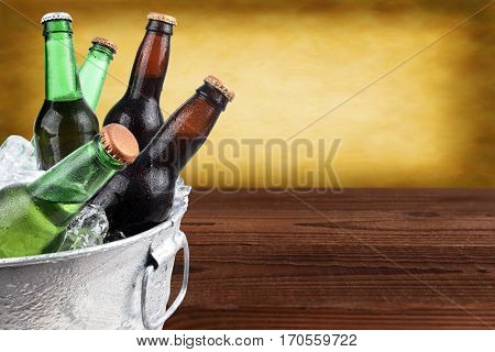 Closeup of a metal ice bucket filled with assorted beer bottles. Horizontal format with copy space and warm background.